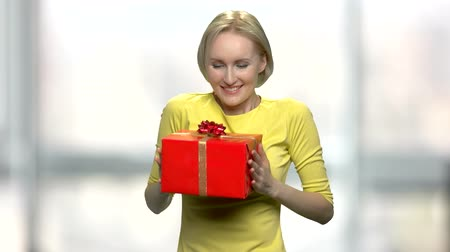 Excited woman embracing gift box. Young caucasian woman in yellow sweater rejoicing her Birthday gift box.