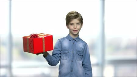 intrigue : Boy in denim shirt holding gift box. Happy kid pointing finger on present box against blurred background. Seasonal sales concept.