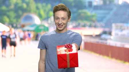 prémie : Young boy giving gift box. Handsome shy guy in casual wear offering gift box with on blurred background. Birthday gift for beloved girl.