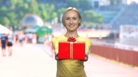 Woman giving gift box on blurred background. Portrait of cheerful girl handing gift box and looking at camera. Give and get.
