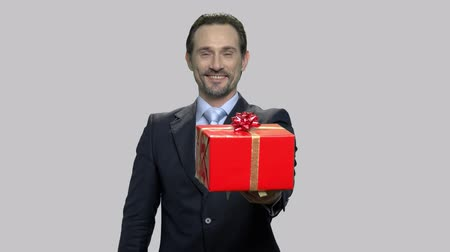 Beautiful gift for you. Middle-aged caucasian businessman giving present box and thumb up sign on gray background. Hot deal holiday. Стоковые видеозаписи