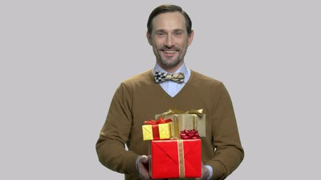 Smiling middle-aged man giving gift boxes. Happy caucasian man presents holiday gifts on gray background. Courier gifts delivery. Стоковые видеозаписи