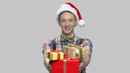 santaclaus : Boy in Christmas hat giving gift boxes. Portrait of satisfied teen guy wearing Santa Claus cap handing Christmas present boxes on gray background.