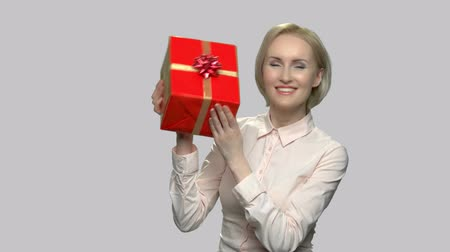 Happy excited woman holding gift box. Surprised emotional woman with present on gray background. Lottery winning concept.