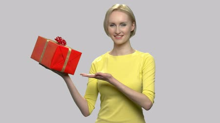 Pretty woman giving gift box. Beautiful woman in yellow sweater presenting gift box on gray background. Bonus for favorite clients.