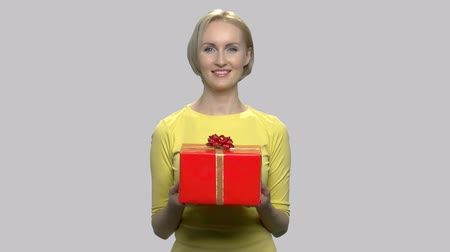 főnyeremény : Charming lady holding gift box. Portrait of beautiful smiling woman with gift box on gray background, front view. Business concept of bonuses discounts.