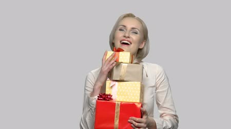 Happy woman with gift boxes on gray background. Beautiful smiling woman received many gifts for Birthday. End of the year bonus.