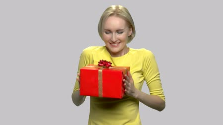 Woman hugging gift box on gray background. Happy satisfied woman giving wrapped present box. Gift for special occassion.
