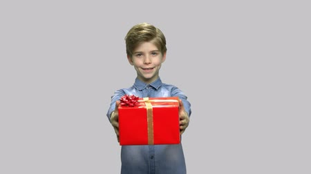 denim : Little boy giving gift box on gray background. Cute child stretching out hands with Birthday gift.