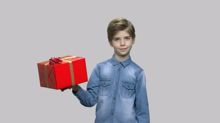 Handsome little boy with large gift box. Portrait of cute stylish kid pointing with finger on gift box over gray background. Start of sales season.