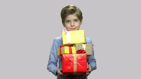Handsome kid holding gift boxes. Cute boy holding many gift boxes and looking at camera on gray background. Holiday gift concept.