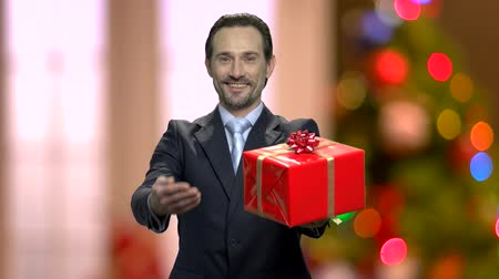 Businessman giving gift box on abstract Christmas background. Smiling man in elegant suit presents gift box against blurred Christmas lights.