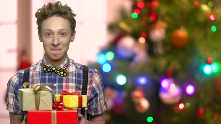 Emotional boy with gift boxes on Christmas lights background. Expressive boy holding boxes with Christmas presents. Winter holiday surprise.