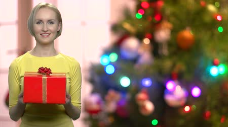 Woman with gift box on blurred Christmas background. Happy smiling woman holding red gift box on defocused Christmas tree background. Merry Christmas and happy New Year.