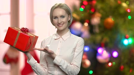 Woman presents Christmas gift box. Pretty smiling business lady showing present box on abstract Christmas background. Gift for winter holidays. Стоковые видеозаписи