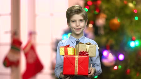 Portrait of cute young man with Christmas gifts. Handsome caucasian boy giving gift boxes on abstract Christmas background. Merry Christmas concept.