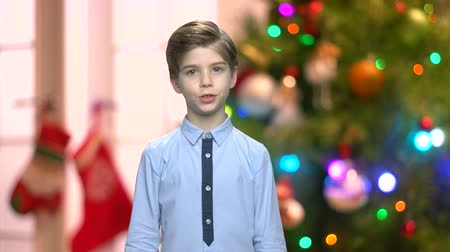 Cute talking boy on abstract Christmas background. Speech of little confident boy on blurred winter holidays backdrop. Стоковые видеозаписи