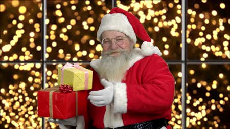 Old traditional Santa Claus with Christmas gifts. Happy authentic Santa Claus giving thumb up on black background with golden lights.