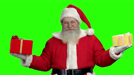 santaclaus : Santa with gifts on green screen. Old authentic Santa Claus holding Christmas gift boxes in both hands. Green chroma key background for keying.