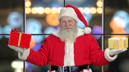 Old happy Santa with Christmas gifts. Winter holiday background. Give happiness to people. Merry Christmas concept.