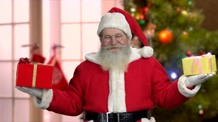 Santa Claus in eyeglasses holding Christmas gifts. Old happy Santa with gift boxes in both hands, front view. Blurred Christmas tree background. Стоковые видеозаписи