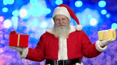 dede : Old bearded Santa holding two gift boxes. Elderly Santa in eyeglasses standing on blue bokeh background. Happiness, noel, festive Christmas time.