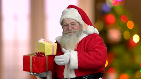 santaclaus : Christmas Santa Claus giving thumb up. Old Santa in eyeglasses holding gift boxes. Defocused Christmas lights background.
