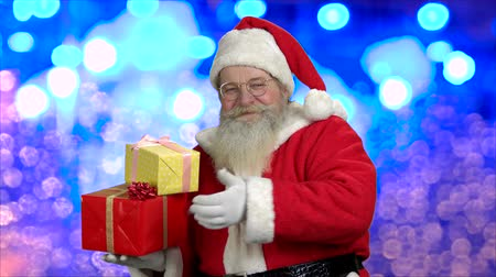 Cute Santa with gifts and thumb up. Old Father Christmas is giving thumb up and smiling on blue bokeh background. Festive seasonal time.