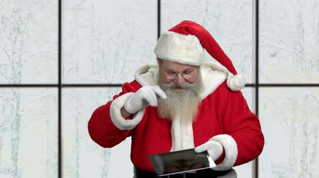 santaclaus : Old Father Christmas showing pc tablet. Smiling Santa holding pc tablet and showing ok sign with fingers. Christmas, holidays, technology and people concept.