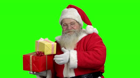 Old smiling Santa showing thumb up. Cheerful Santa Claus holding gift boxes on green screen background. Special Christmas offer.
