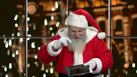 rekomendacja : Santa Claus showing blank digital tablet. Happy elderly Santa holding pc tablet and showing ok gesture. Evening city background.