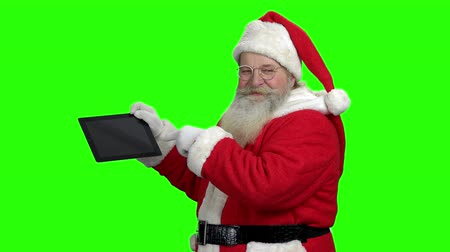 Santa showing pc tablet on green screen. Old bearded Santa with digital tablet on Chroma Key background. Christmas season sales.