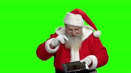 Santa showing pc tablet with blank screen. Cheerful Santa Claus giving ok gesture while holding computer tablet. Green Chroma Key background for keying.