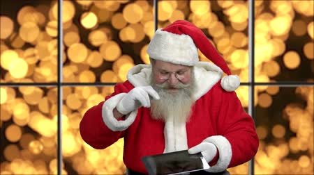 santaclaus : Portrait of old Santa with digital tablet. Senior Santa showing pc tablet and ok sign on golden bokeh background. Christmas and holiday season sales.