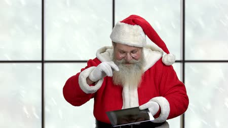 seasonal sale : Santa presents computer tablet with blank space. Santa Claus showing pc tablet and ok gesture. Christmas presents selling concept. Stock Footage