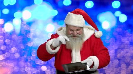Old-fashioned Santa showing digital tablet. Authentic Santa in eyeglasses on blue bokeh background. Festive seasonal time.