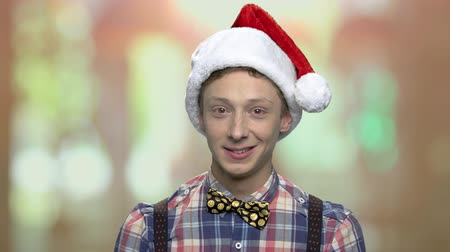 Portrait of teen boy in Christmas hat. Cheerful teen guy in Santa Claus cap looking at camera.