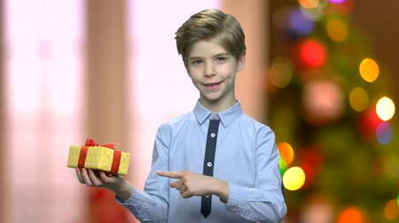 newyear : Portrait of cute boy with Christmas gift box. Lovely child pointing with finger on gift box. Defocused Christmas background with shining lights.