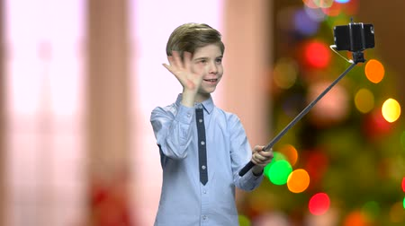 newyear : Cute boy using selfie stick. Cheerful young boy taking selfie with peace gesture. Funny child making grimace while holding monopod. Blurred Christmas background. Stock Footage
