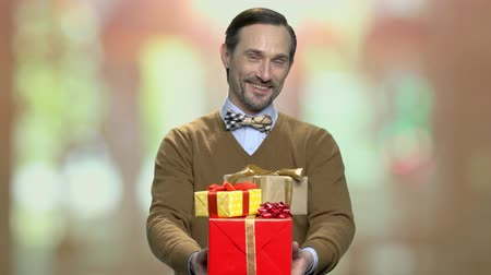 newyear : Man with gift boxes looking at camera. Handsome middle-aged man holding stack of gift boxes on blurred background. Gifts for Womens Day.