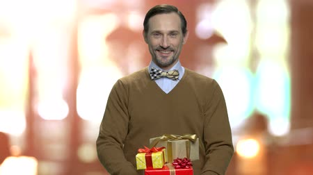 intrigue : Attractive man giving gift boxes. Smiling middle-aged man handing present boxes to camera. Get your holiday prize.