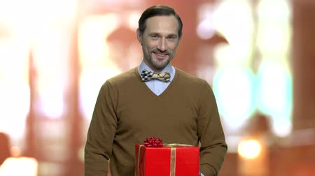intrigue : Portrait of mature man offering gift box. Delivery man giving festive gift box to camera on blurred background.
