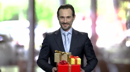 prémie : Smiling attractive businessman holding gift boxes. Handsome man with pile of gifts looking at camera on blurred background.