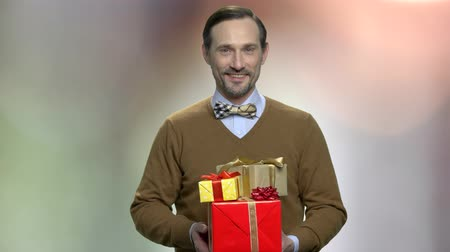 intrigue : Attractive man with gift boxes. Handsome smiling middle-aged man holding pile of gifts and looking at camera. Holiday commercial offer. Stock Footage