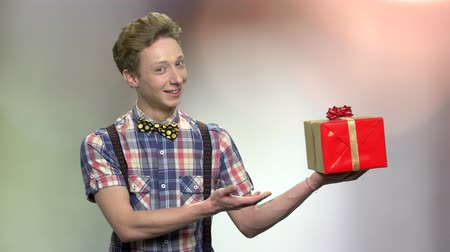 főnyeremény : Elegant teen boy presenting gift box. Cute caucasian teen guy wearing shirt with bow-tie. Gift for special occasion. Holiday offer concept. Stock mozgókép