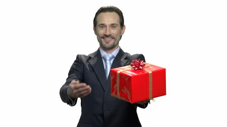 prémie : Handsome executive presenting gift box. Stylish caucasian businessman offering wrapped gift box. Holiday celebration concept.