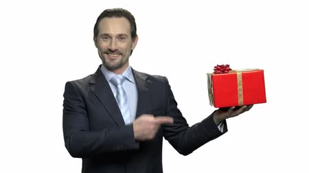 bonus : Portrait of businessman presenting gift box. Smiling man in formal suit pointing with finger on gift box and looking at camera. Holiday special offer. Stock Footage