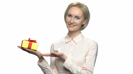 promocional : Pretty blonde with gift box on her palm. Beautiful caucasian business woman posing with gift box. Special offer for you. Holiday celebration concept.