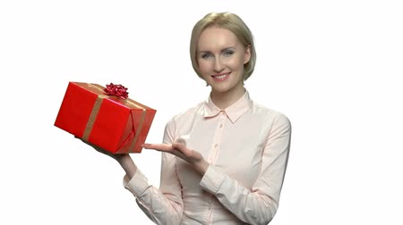 prémie : Smiling woman showing red gift box. Cheerful caucasian girl presenting beautiful gift box. Holiday deal concept.