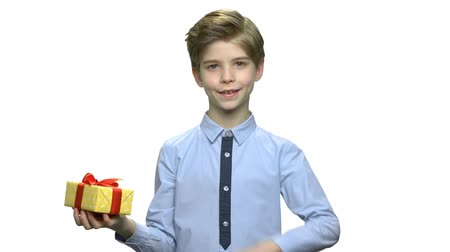 bonus : Cute smiling kid with gift box. Handsome little boy pointing on gift box with finger while holding it over white background. Holiday surprise concept. Stock Footage